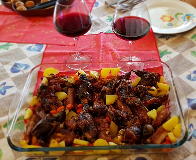 Tordi al forno con patate e bicchiere vino rosso